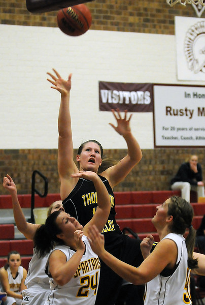 Thompson Valley High School senior Jordan Sibrel takes a shot while surrounded by Berthoud defenders, from left, Lindsey Loberg, Danielle Wikre and Amy Loberg in the second quarter of their game Thursday at BHS. The Eagles won, 54-28.