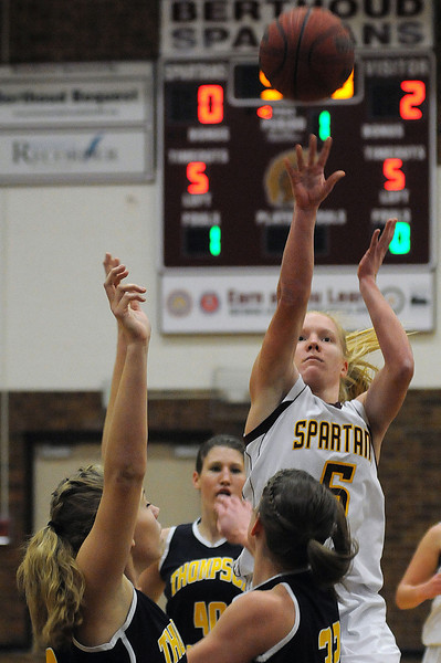 Senior Amy Ekart of Berthoud High School rises above junior Alexis Hunt, left, and senior Morgan Sibrel, center, of Thompson Valley High School on her way to the basket during the first quarter of Tuesday night's game at Berthoud High School. The Eagles won the game 52-40.