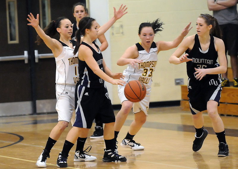 Mountain View High School freshman Brittney Bjork, front, passes the ball to teammate Erin Stumbaugh while Thompson Valley's Brittany Pascal, left, and Alexis Hunt (33) defend on the play in the first quarter of their game Thursday at TVHS.