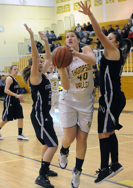Thompson Valley High School senior Jordan Sibrel (40) takes the ball to the basket between Mountain View's Kellie Eastman, right, and Rikelle Berry in the third quarter of their game Thursday night at TVHS. At rear from left are Hannah Hoffman and Lauren Mickelson.