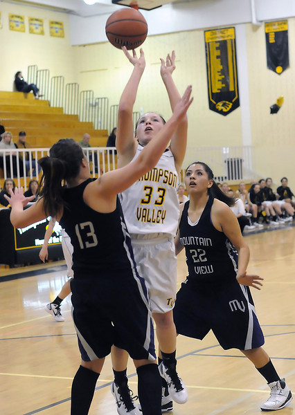 Thompson Valley High School senior Alexis Hunt (33) puts up a shot between Mountain View defenders Kellie Eastman (13) and Nekeshia Gonzales in the first quarter of their game Thursday night at TVHS.
