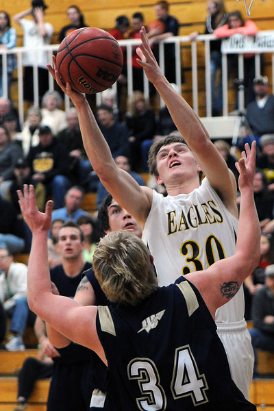 Thompson Valley High School senior Karsen Buschjost, top, pulls down a rebound between Frederick's Ryan Miller, (34) and Jayden McGraw in the second quarter of their game Tuesday, Feb. 21, 2012 at TVHS.