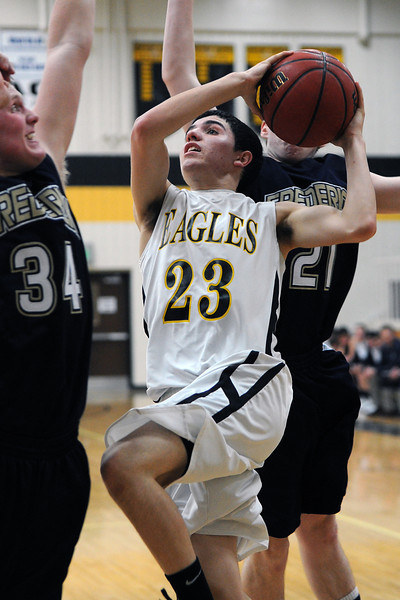 Thompson Valley High School sophomore Mike Olivas, middle, drives to the basket between Frederick defenders Ryan Miller, left, and Nathan Harrison in the third quarter of their game Tuesday, Feb. 21, 2012 at TVHS.