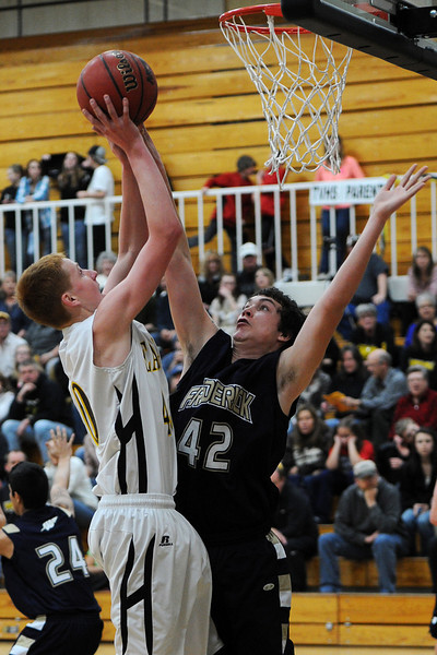 Thompson Valley High School sophomore Collin Smith, left, puts up a shot over Frederick's Jayden McGraw in the second quarter of their game Tuesday, Feb. 21, 2012 at TVHS.