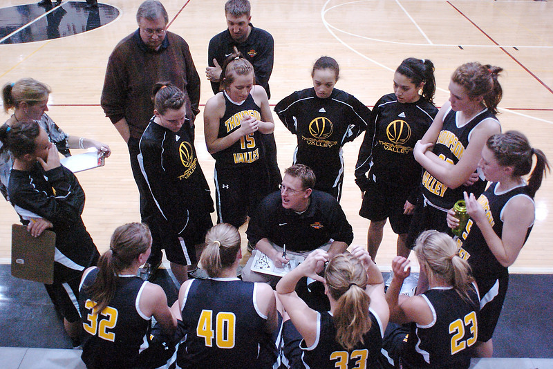 Thompson Valley High School girls basketball head coach Chad Walker, kneeling in center, talks to his players during a timeout Tuesday at Roosevelt.