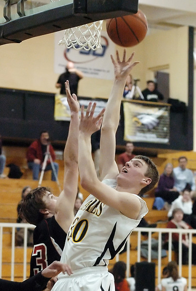 Thompson Valley High School sophomore Karsen Buschjost takes a shot over Skyline's Brandon Dabney in the second quarter of their game Tuesday, Jan. 26, 2010 at TVHS.