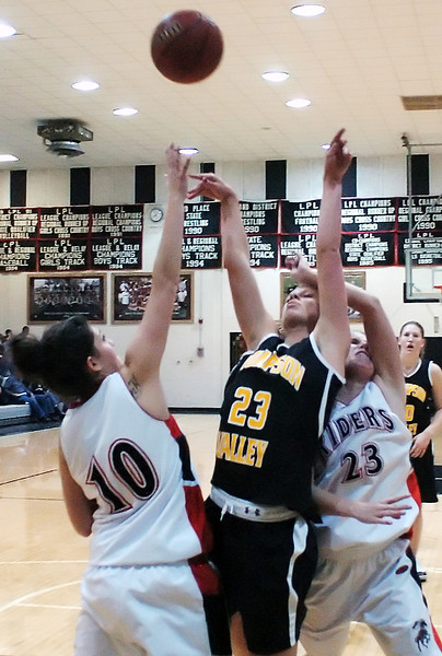 Thompson Valley High School's Sydney Paulsen, is fouled as she goes up for a shot between Roosevelt defenders Kaylee Longoira, left, and Lynae Dillehay in the second quarter of their game on Tuesday, Jan. 5, 2010 at RHS.