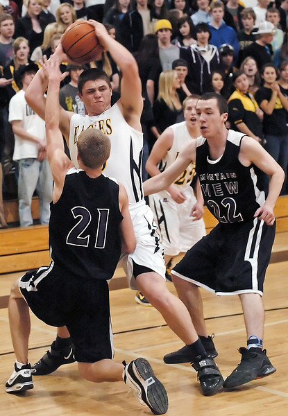 Thompson Valley High School junior Caleb Carlson looks for an open teammate while being pressured by Mountain View's Darryl Beemer, left, and Spencer Stetler while Zac McMorris, rear, looks on in the second quarter of their game Friday night at TVHS.