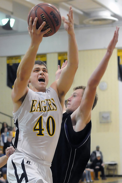 Thompson Valley High School senior Caleb Carlson (40) takes the ball to the basket in front of Mountain View's Zach Watson in the fourth quarter Tuesday night at TVHS.