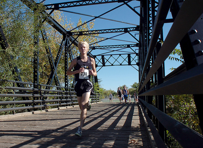 TV's Gus Waneka crosses the bridge during a cross country meet Thursday at Fairgrounds Park in Loveland.