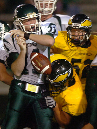 Niwot quarterback #11 looses the ball as Thompson Valley's #52, back, and #54 tackle him Friday during their game at Ray Patterson Stadium.