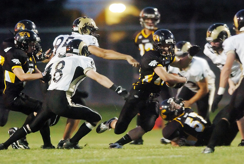 Thompson Valley High School running back Noah Harold, center, is pursued by Green Mountain defenders on a run play in the first half of their game Thursday, Sept. 16, 2010 at Patterson Stadium.
