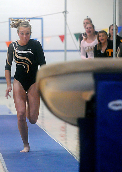 With teammates cheering in the distance, Thompson Valley High School's Ashleigh Waterland approaches the vault during the Colorado State Gymnastics  Championships on Saturday at Thornton High School.