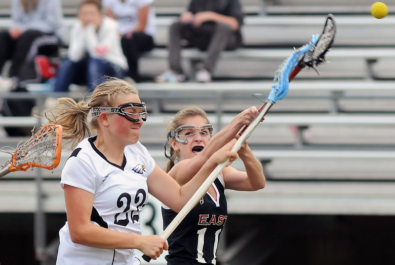 Thompson Valley High School's Maggie Mawhinney, left, takes a shot in front of Denver East defender Emma Dayney in the first half of their game Wednesday at Patterson Stadium. Thompson Valley lost, 18-3.
