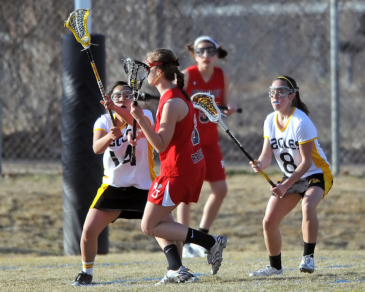 Thompson Valley High School's Dana Olsen, right, and Lanie Matsumoto defend against Regis Jesuit attacker Maggie Rogan while Taylor Walker, back, looks on in the second half of their match on Friday, March 18, 2011 at Patterson Stadium. The Eagles lost, 17-6.