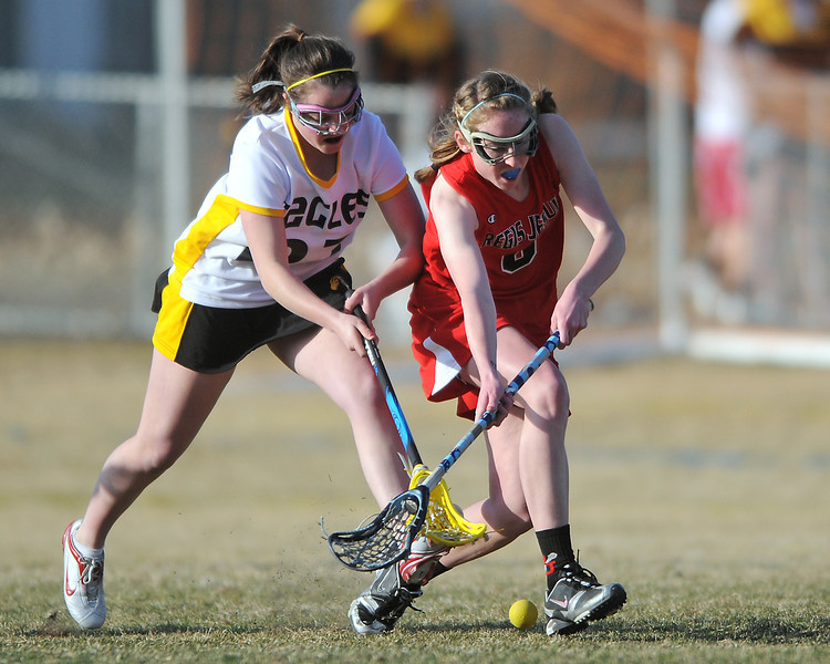 Thompson Valley High School's Meghan Loury, left, battles Regis Jesuit's Faye Hubregsen for control of the ball in the second half of their match on Friday, March 18, 2011 at Patterson Stadium. The Eagles lost, 17-6.