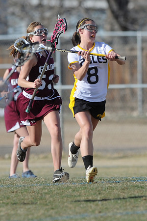 Thompson Valley High School's Dana Olsen, right, gets ready to pass the ball ahead of Golden's Sage Windell in the first half of their game Wednesday, March 14, 2012 at Patterson Stadium.