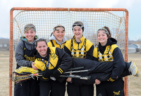 Thompson Valley High School Lacrosse seniors hold their coach Liz Melahn up Thursday before practice. From left they are Kennedi Conradson, 17, Maggie Mawhinney, 17, Megan Golliher, 18, and Meghan Loury, 18. Melahn has coached the girls since about seventh grade. Photo by Jenny Sparks