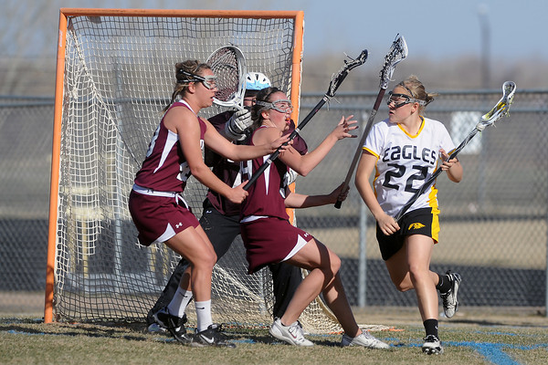 Thompson Valley High School's Maggie Mawhinney, right, works around the net against Golden defenders Macell Sprackling, left, and Bonnie Criss and goalie Alexa Sonnefeld, back, in the first half of a game on Wednesday, March 14, 2012 at Patterson Stadium.
