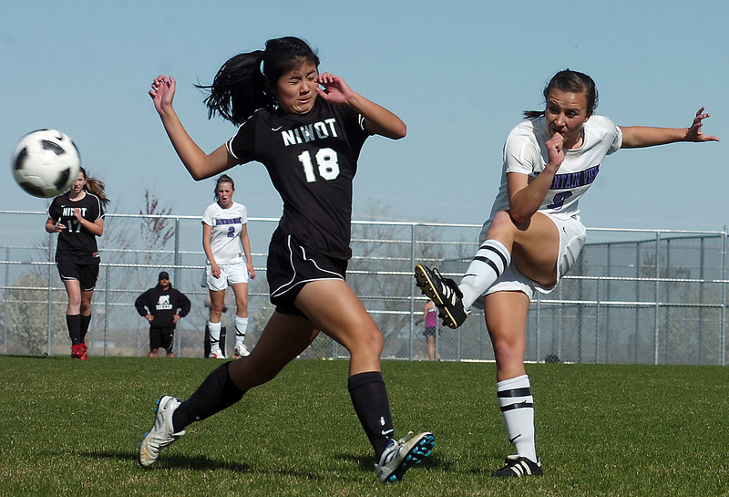 Mountain View's #9 Kayla Grimes kicks the ball past Niwot's #18Cindy Yie during their game Thursday.