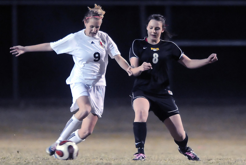 Loveland High School senior Chelsea Glanzer, left, and Thompson Valley junior Jessica Moran battle for control of the ball in the first half of their game Tuesday night at Patterson Stadium. The Eagles won, 2-1.