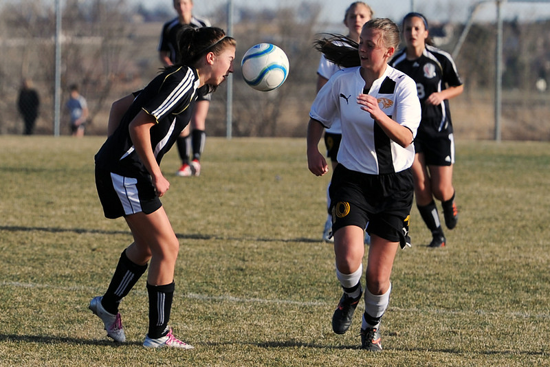 Loveland High School's Allison Gleason, left, heads the ball away from Thompson Valley's Kaylyn Maston in the first half of their game Tuesday, March 20, 2012 at the Mountain View soccer field.