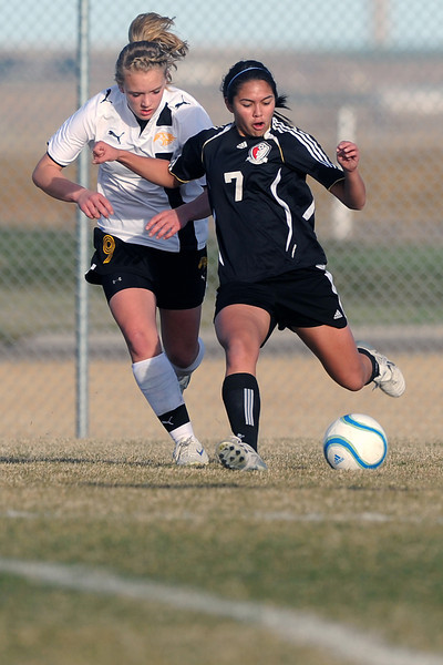 Loveland High School junior Greta Grainda, right, takes a shot in front of Thompson Valley's Jordan Paulsen in the first half of their game Tuesday, March 20, 2012 at the Mountain View soccer field.