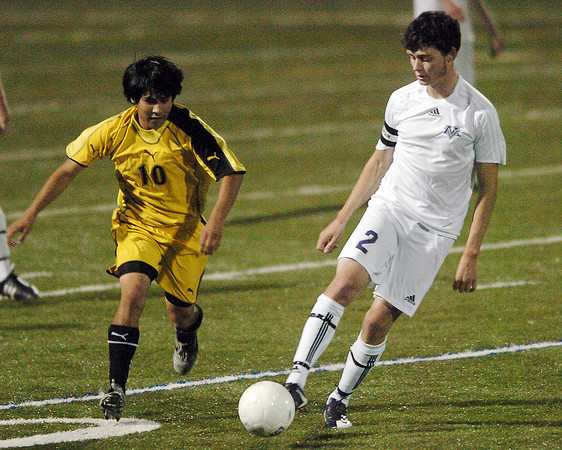 Mountain View High School senior Craig Lehmeier, right, passes the ball in front of Thompson Valley's Ricardo Apolonio in the first half of their game Monday night at the Loveland Sports Park. Mountain View won, 1-0.