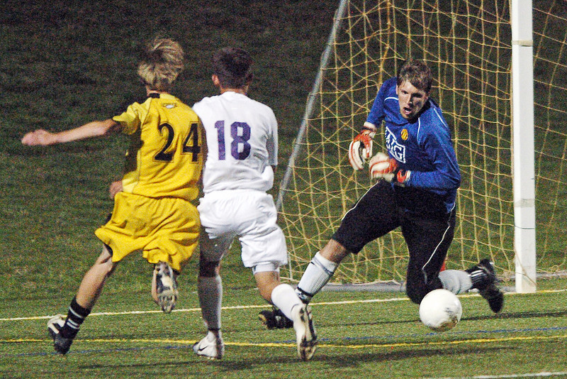 Mountain View High School goalie Quinn Benson makes a stop in front of teammate Corey Muse (18) and Thompson Valley's Jesaja Lemke in the first half of their game Monday night at the Loveland Sports Park. The Mountain Lions won, 1-0.