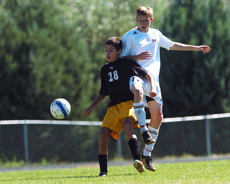Thompson Valley High School's Quin Scanlon, left, and Berthoud's Ryan Cox go after a loose ball in the first half of their game Saturday morning at Marr Field in Berthoud. Scanlon scored a goal in the Eagles' 4-0 win over the Spartans.