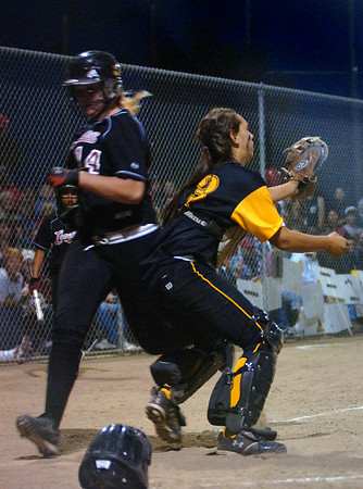 Loveland High's #14 Chelsea Brewer hits home plate before Thompson Valley's catcher #13 Cheyenne Delaney tags her out during their game at Centennial Field Tuesday night.