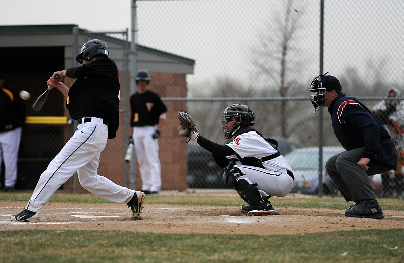Thompson Valley High School senior Teague Mcfadden connects with a pitch while Loveland High School senior Quinn Konitshek looks on during the third inning of a windy and cold game Monday evening at Bill Swift Field in Loveland, Colo.