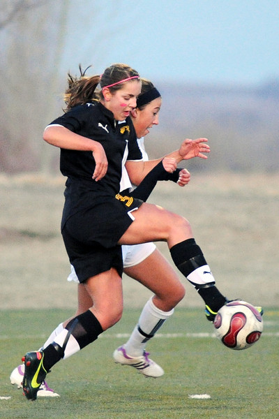Thompson Valley High School's Tarissa Zeigler, front, collides with Loveland's Allison Gleason as they go after the ball in the first half of their game on Friday, April 12, 2013 at the Loveland Sports Park.