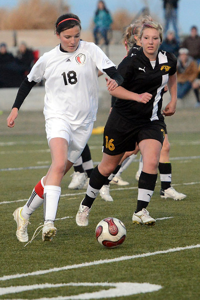 Loveland High School senior Lauren Spencer, left, and Thompson Valley senior Cassie Baalke track down the ball in the first half of their game on Friday, April 12, 2013 at the Loveland Sports Park.