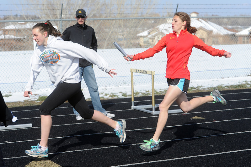 Thompson Valley High School sophomore Lindsey Kroboth, right, passes the baton to teammate Megan Irvine while working on relay handoffs during practice Tuesday, April 23, 2013 at TVHS.