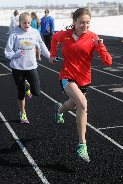 Thompson Valley High School sophomore Lindsey Kroboth, right, sprints away from freshman Maren Janda after receiving the baton from her while practicing handoffs for the 800-meter medley relay on Tuesday, April 23, 2013 at TVHS.