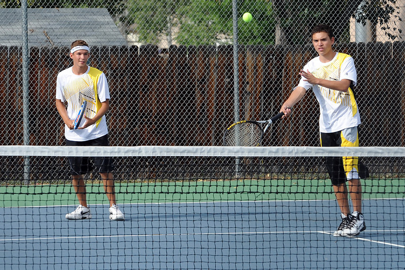 Thompson Valley High School senior Justin Hartzog, left, looks on while No. 2 doubles teammate Grant Rohrbouck hits a shot at the net during their match against Loveland's Colton Poore and Tanner Foster on Thursday, Aug. 30, 2012 at TVHS. Hartzog and Rohubouck won, 6-3, 6-1.