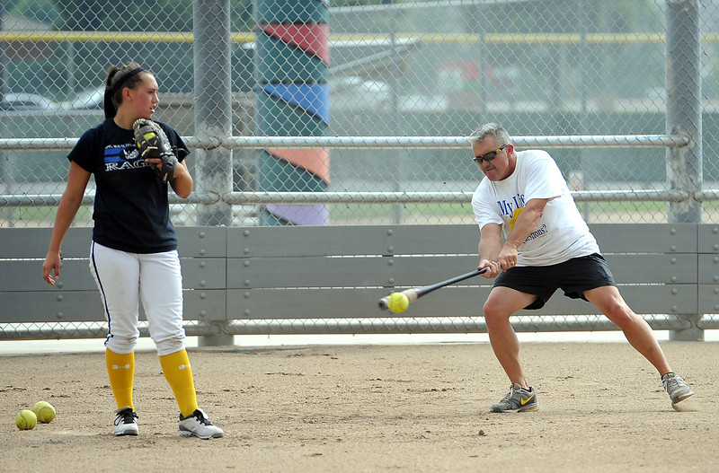 Thompson Valley softball coach Bryon Rutherford hits a ball to players during practice Monday at Centennial Fields in Loveland. Catcher Cheyenne Delaney keeps her eye on the ball.