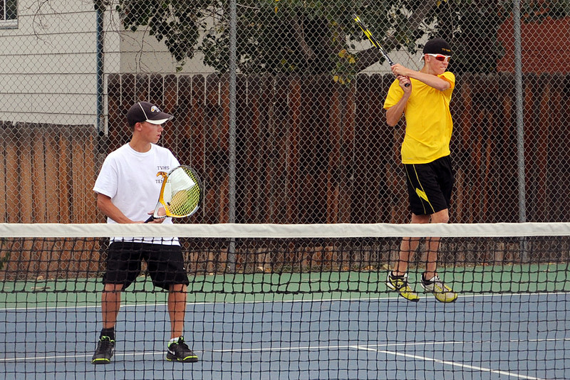 Thompson Valley High School sophomore Jacob Schafer, right, follows through on a backhand while No. 4 doubles teammate Wesley Wilson looks on during their match against Loveland's Tyler Helfrich and Garett Donaldson on Thursday, Aug. 30, 2012 at TVHS.