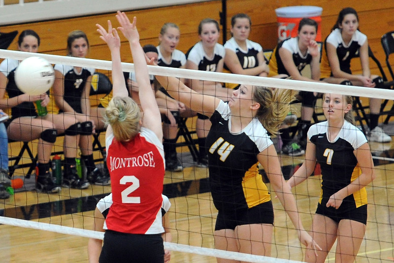 Thompson Valley High School's Taylor Moran (14) spikes the ball past Montrose's Emily Sanburg (2) while Carly Feuerstein (7) looks on during set one of their match Saturday, Nov. 3, 2012 at TVHS.