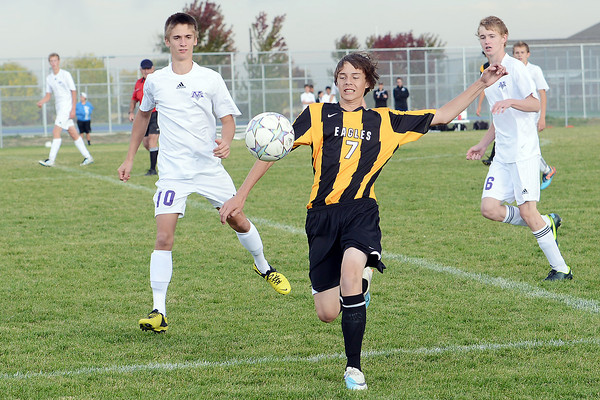 Thompson Valley High School's Hunter Williams, middle, eyes the ball between Mountain View's Lorenzo Rigatti, left, and Grayson Pike in the second half of their match on Wednesday, Oct. 3, 2012 at MVHS.