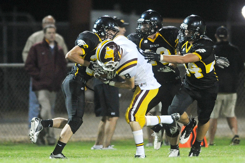 Windsor High School quarterback Blake Bunday (8) is tackled by Thompson Valley defenders Tanner Knaus, left, Brian Herr and David Eusea in the second quarter of their game on Thursday, Sept. 20, 2012 at Patterson Stadium.