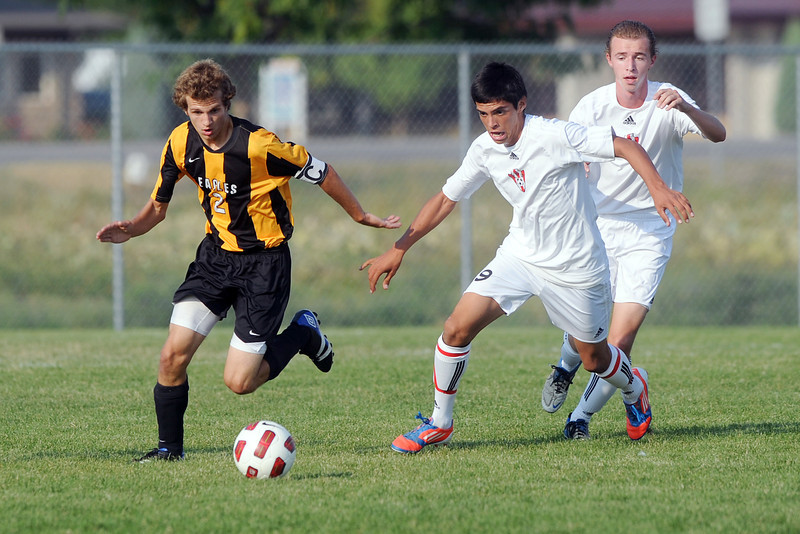 Thompson Valley HIgh School's Nash Doughman, left, and Loveland's Cristian Buendia, middle, and Andrew Woodward track down the ball in the first half of their match on Friday, Sept. 21, 2012 at the Mountain View soccer field.