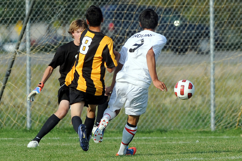 Loveland High School's Cristian Buendia, right, scores a goal past Thompson Valley goalie Jacob Sievers, back, and defender Colton Bierbaum in the first half of their match on Friday, Sept. 21, 2012 at the Mountain View soccer field.