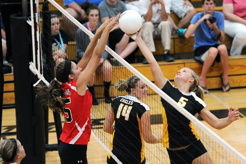 Loveland High School's Lexi Veltri, left, goes up against Thompson Valley's Hannah McCrimmon (5) in set two of their match Friday, Aug. 31, 2012 at TVHS.