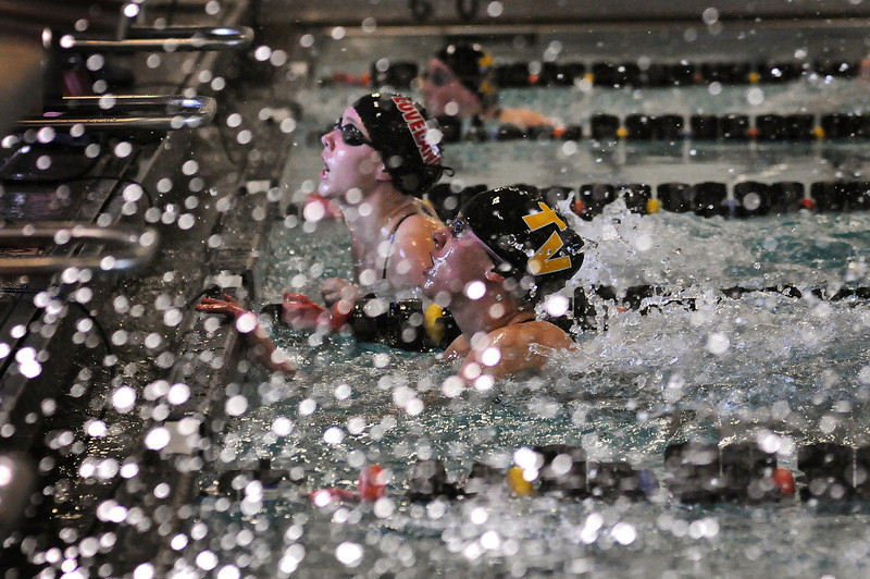Maggie Varuska of Thompson Valley High School, foreground, and Jordan Mathews look to the scoreboard after swimming the 50-yard freestyle event during Thursday evening's Loveland City Meet at Mountain View High School. Varuska just edged out Mathews by .06 with a time of 25.02.
