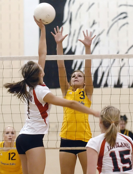 Thompson Valley High School junior Lindsey Laws (3) goes up to block Loveland's Pam Janicek while Ciara Krening (12) and Andrea Alles (15) look on during game one of their match on Friday, Oct. 8, 2010 at TVHS. The Eagles won, 3-0.