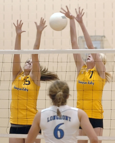 Thompson Valley High School's Meghan Miller, left, and Erin Marolf go up for a block while Longmont's Tambre Haddock looks on during game one of their match on Thursday, Sept. 30, 2010 at TVHS.