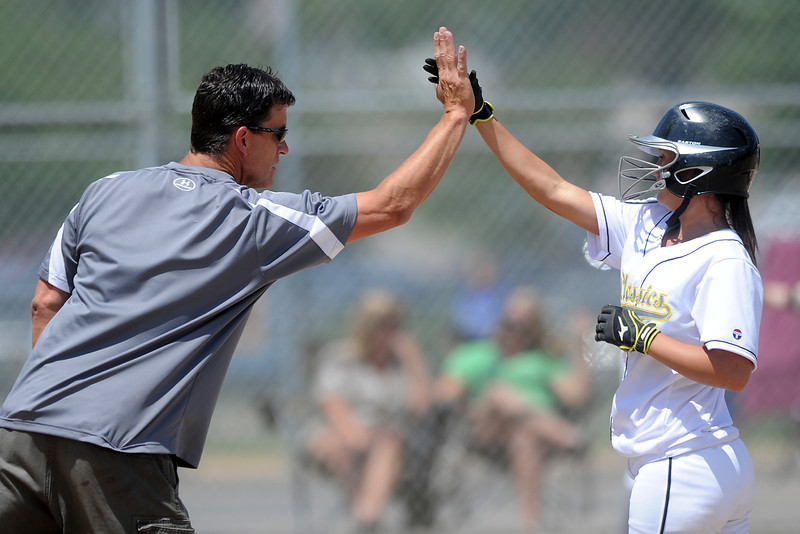 First base coach John Williams gives Chanley Burge a high five after she hit a single during a game against the Majestix at the Barnes Softball Complex on Friday, July 13, 2012.