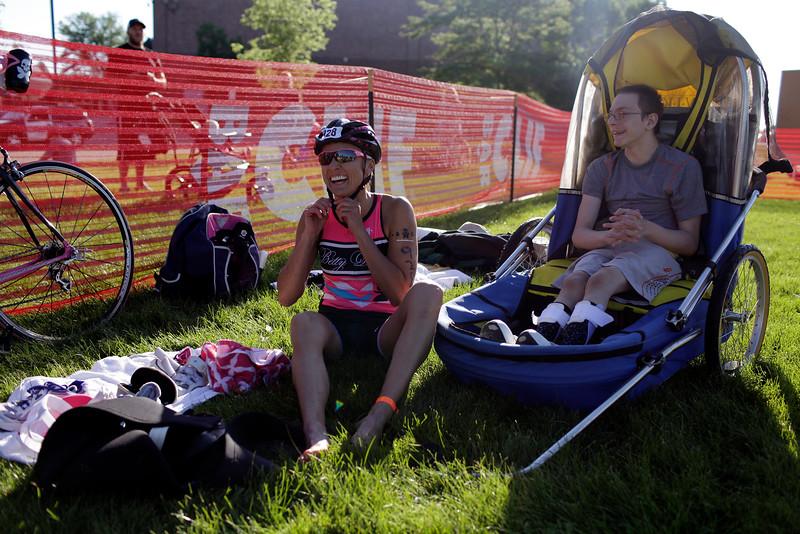 Kristina Jensen with Andrew Stinson get suited up for the bike portion of the Loveland Lake to Lake Triathlon on June 27, 2015. (Photo by Trevor L Davis/Loveland Reporter-Herald)
